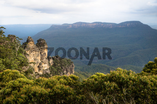 Two of the three sisters rock formation in the Blue mountains with massive mountain, Katoomba, New South Wales, Australia