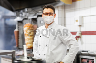 male chef with in face mask at kebab shop kitchen