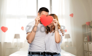 couple hiding behind red heart on valentines day