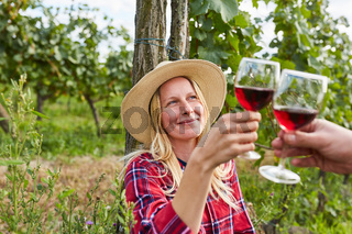 Blonde Frau beim Anstoßen mit Rotwein