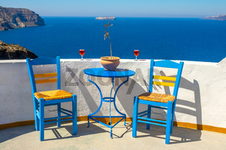 Two Chairs and Two Glasses on a Sunny Rocky Shore