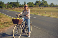 Middle-aged blond woman shopping for groceries on her bicycle