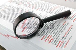 Magnifying glass focussed on the word quality. Quality assurance control enhancement business concept
