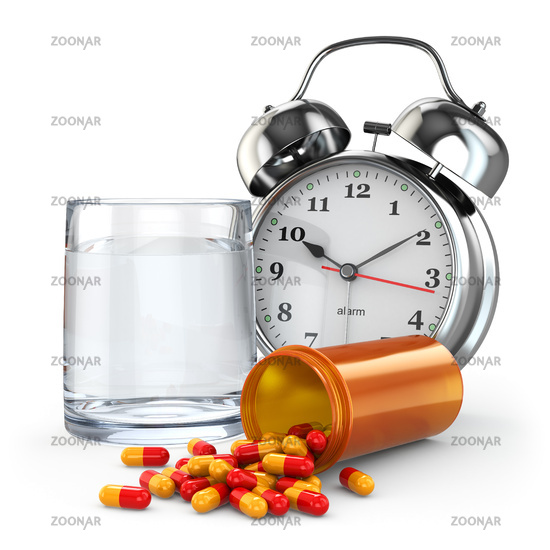 Medication time. Pills, water glass and alarm clock.