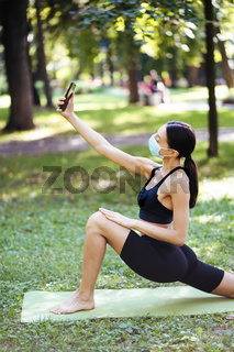 Young sport girl take selfie on a smartphone outdoors on nature.