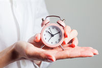 Woman in white shirt holds alarm clock