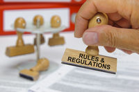 rules and regulations printed on rubber stamp in hand