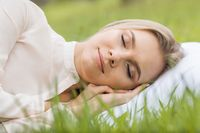 Woman sleeping on pillow in grass