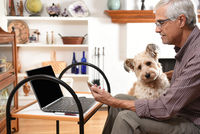 Mature man working from home with his laptop and cell phone and his pet dog on his lap, during the C