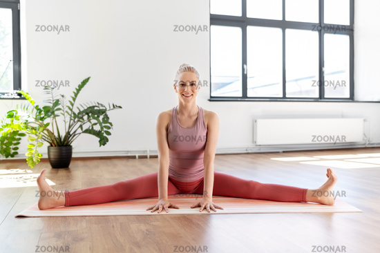 young woman doing full split on mat at home