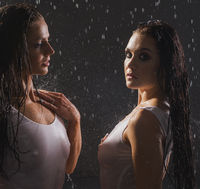 Two pretty girls in wet tops in rain together
