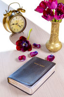 Holy Bible and old gold alarm clock with flowers