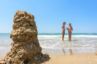 In the foreground a tower of sand, in the background two girls on the seashore