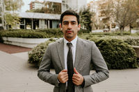 Confident and successful young businessman wearing suit and tie, posing outdoor.