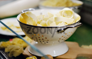 Close up bowl with fresh uncooked fettuccine or tagliatelle Italian traditional type of pasta