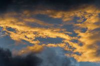 Golden fluffy clouds illuminated by disappearing rays at sunset and dark thunderclouds in sky