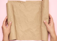 two male hands hold a roll of brown paper on a pink background