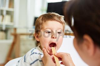 Kinderarzt untersucht Kind mit Mandelentzündung