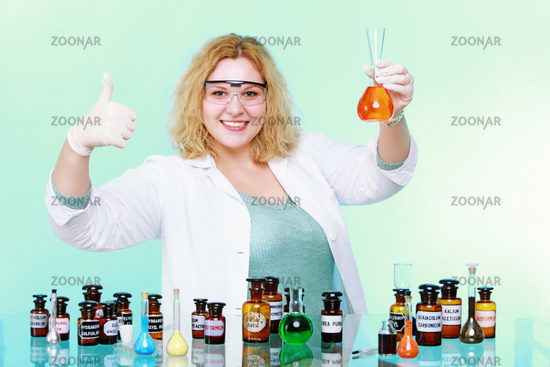 Happy chemist woman or girl student or female laboratory assistant or scientific researcher with chemical glassware test flask