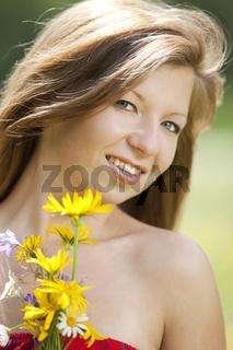 Laechelndes Maedchen mit Blumen in der Hand