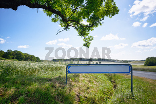 Road sign with an arrow in idyllic nature