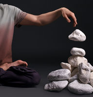 Man sitting in yoga pose with white stones near by