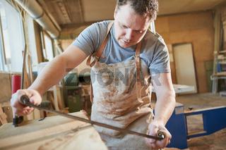 Schreiner beim Holz entrinden mit dem Zugmesser