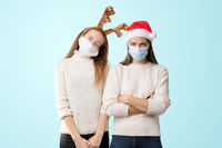 Caucasiam young women on white background with santa hat and reindeer. Christmas quarantine