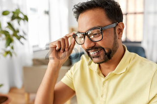 happy smiling indian man in glasses at home office