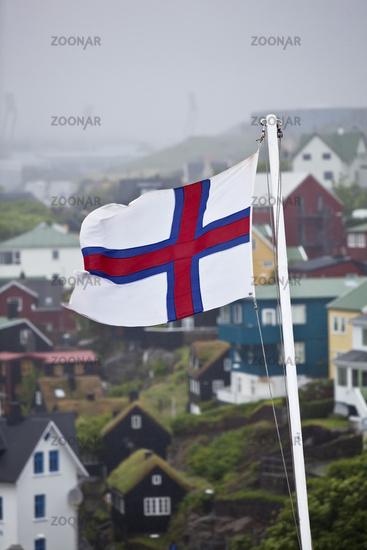 Flag of Faeroeer in front of houses in the fog, Thórshavn, Faeroeer, Føroyar, Denmark, Europe