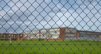 High School Building Behind A Fence