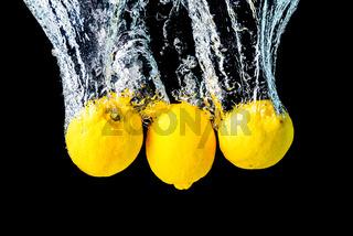 Lemons splash into water and sinking on black background.