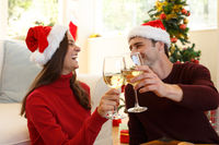 Couple wearing santa hat looking at each other smiling and toasting while sitting in the living room