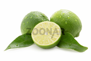 Limes with leaf - one sliced - isolated against white