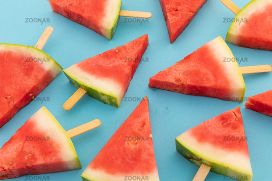 Close up of multiple watermelon triangles on wooden sticks on blue background