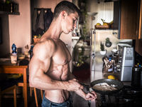 Shirtless male bodybuilder cooking in kitchen at home