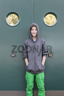 portrait of a smiling male teenager in front of a green metal door, with two portholes