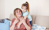 Happy woman with little girl at home