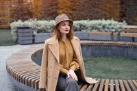 Charming french young woman in an autumn beige coat and plaid hat sits on a round bench flowerbed waiting for her date or girlfriends. Tinted photo