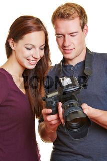 Fotograf zeigt Model Fotos auf Kamera