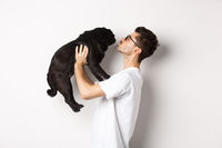 Profile of handsome young man kissing small cute dog face. Hipster guy loving his pug, standing over white background