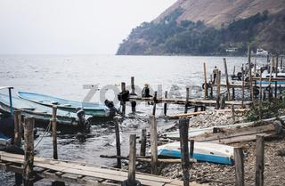 Local man with cowboy hat sitting at dock along lake Atitlan at the coast of Santa Cruz la Laguna, Guatemala