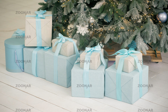 New Year gifts under Christmas tree on white floor