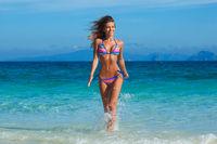 Girl running in sea waves