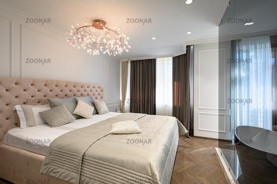 Big comfortable double bed in elegant classic bedroom