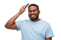 happy african american man brushing hair with comb