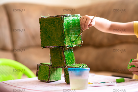 Child paints a paper handicraft toy in green color. Home leisure and self-development
