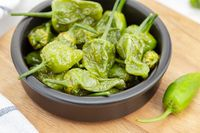 Close up of Cooked Padron peppers in a a bowl on wooden table