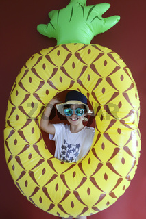 Pretty emothional child wear a hat and sunglasses on a red background. Copy space, daylight