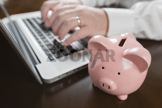 Piggy Bank Near Male Hands Typing on Laptop